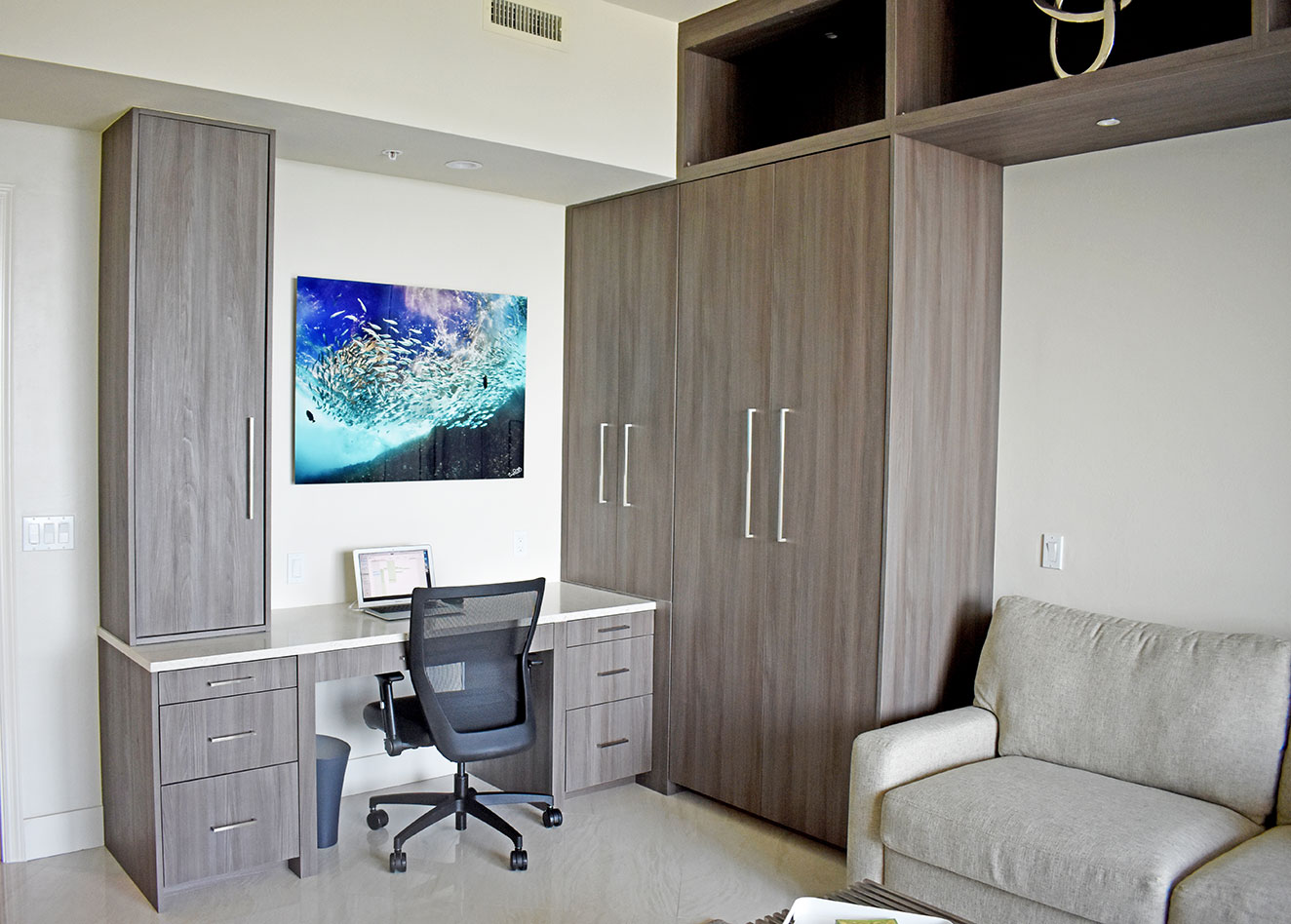 Comfortable and sleek den / office with custom desk and storage